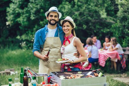 Happy friends having fun grilling meat enjoying barbecue party Imagens
