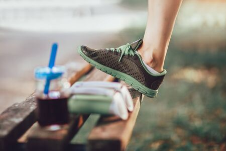 Woman raised her leg on the bench, after training in nature Imagens