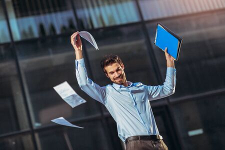 Portrait of a young happy businessman outside the office building with raised hands Imagens