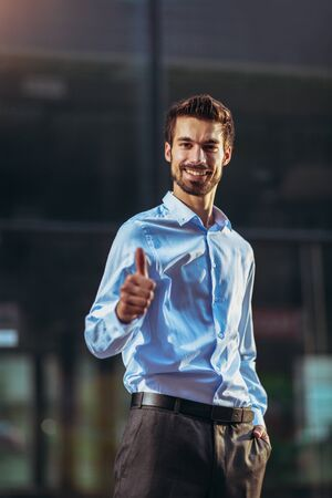 Young handsome businessman showing thumbs up outdoor. Imagens