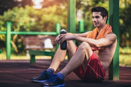 Tired athletic man in sportswear resting after workout outdoor.
