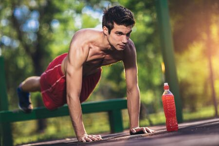 Picture of a young athletic man doing push ups outdoors. Imagens