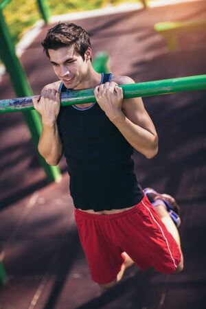 Fitness man doing workouts on horizontal bar outdoors Imagens