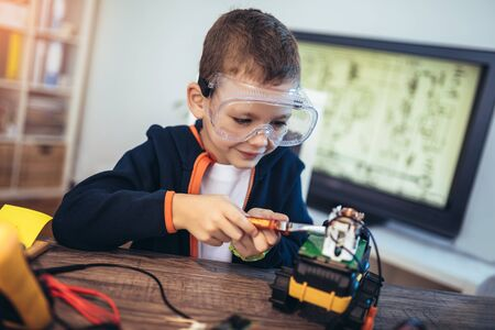Happy smiling boy constructs technical toy. Technical toy on table full of details Imagens