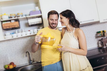 Pregnant woman with husband in the kitchen