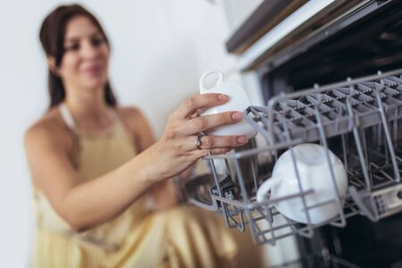 Young Woman Arranging Plates In Dishwasher At Home. Selective focus.
