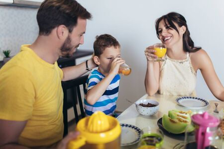 Family Eating Breakfast At Kitchen Table Imagens