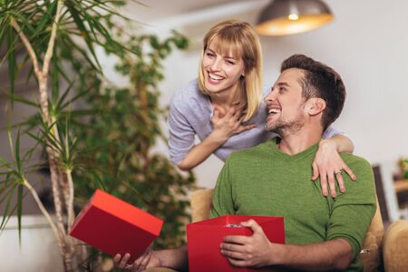 Happy man receiving a present from his girlfriend while sitting on the sofa Imagens