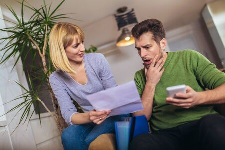 Photo of a young couple embracing and calculating the bills at home.