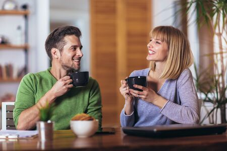 Couple talking in the night in the living room at home and drink tea