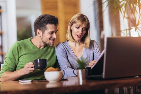 Couple sitting at the desk at home read notice paper check bills or bank account balance
