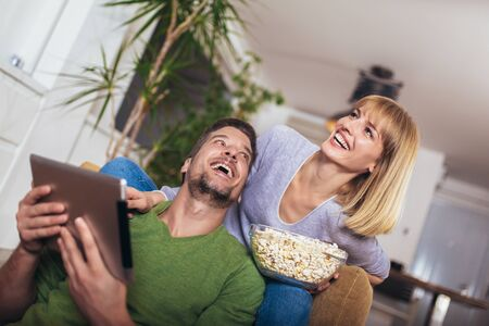 Young couple sitting on the couch in a living room and looking at digital tablet