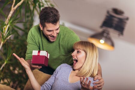 Happy woman receiving a present from his boyfriend while sitting on the sofa Stock fotó