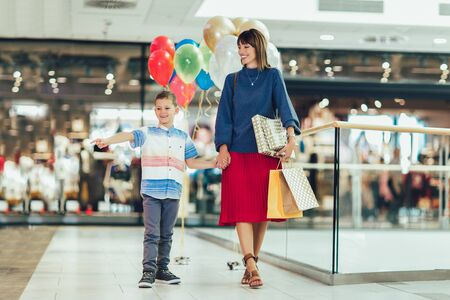 Mother and son having fun in shopping mall toghether. Stock Photo