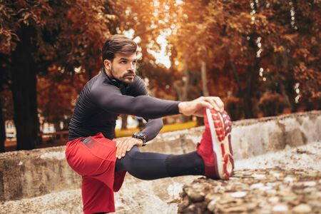 Sport man stretching at the park autumn, doing exercises.  Stok Fotoğraf