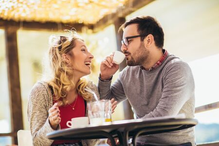 Beautiful loving couple sitting in a cafe enjoying in coffee and conversation. Reklamní fotografie