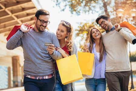 Friends having fun in shopping together, holding shopping bags and credit card. Stok Fotoğraf