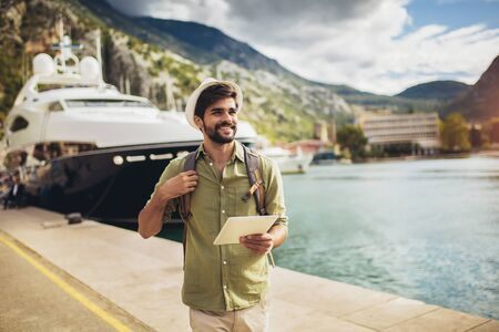 Young man walking by the harbor of a touristic sea resort with boats on background, holding digital tablet.