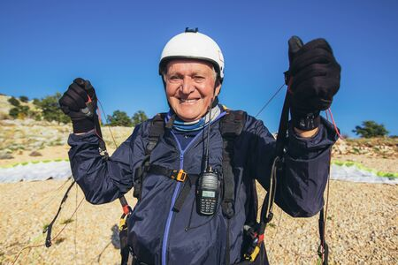 Senior paraglider on the ground prepairs to fly.