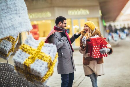 Young couple dressed in winter clothing holding gift boxes outdoor. They eat pretzels.
