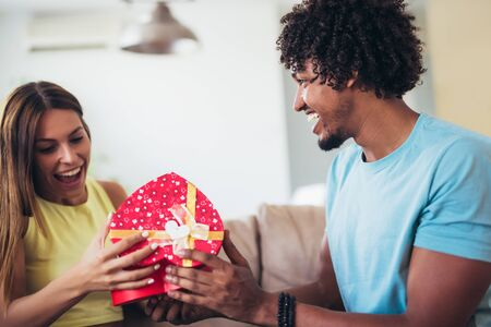 Man giving a surprise gift to woman at home.