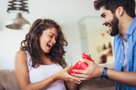 Beautiful young couple is celebrating at home. Handsome man is giving his girlfriend a gift box Imagens