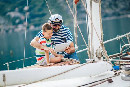 Grandfather and grandson are looking tablet on yacht sail boat. Banco de Imagens