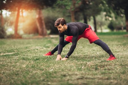 Sport man stretching at the park, doing exercises. Stok Fotoğraf