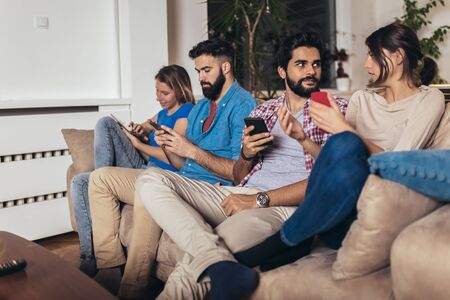 Four happy friends using their mobile phones sitting on a sofa at home