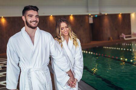 Happy couple enjoying treatments and relaxing at wellness spa center Фото со стока
