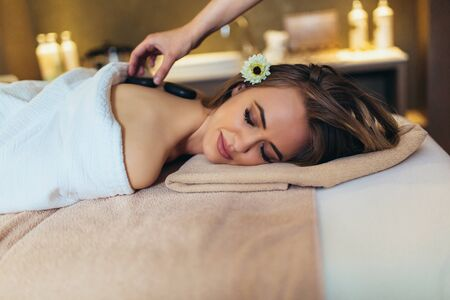 Beautiful woman relaxing in spa salon with hot stones on body.