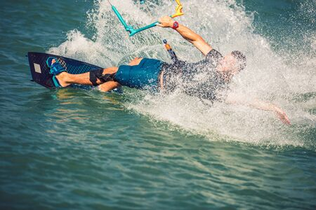 Professional kiter makes the difficult trick on a river. Kitesurfing Kiteboarding action photos man among waves quickly goes Banco de Imagens