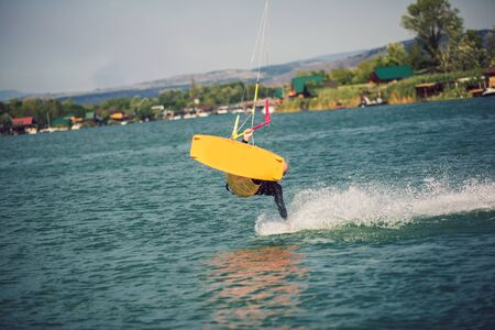 Professional kiter makes the difficult trick on a river. Kitesurfing Kiteboarding action photos man among waves quickly goes Banque d'images