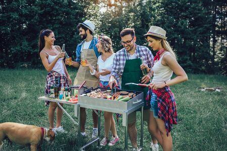 Junge Freunde, die Spaß beim Grillen von Fleisch haben und Grillparty genießen.