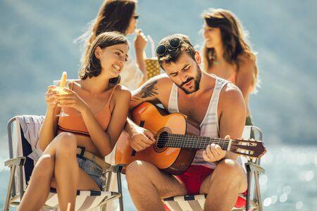 Junge Freunde, die sich an einem sonnigen Tag am Strand amüsieren. Party Zeit. Standard-Bild