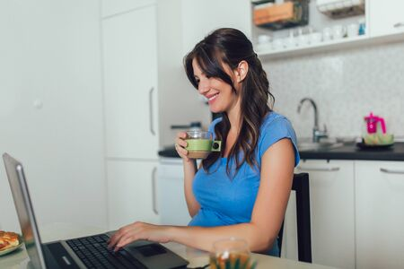 Pregnant woman with belly working as freelancer with laptop at home.