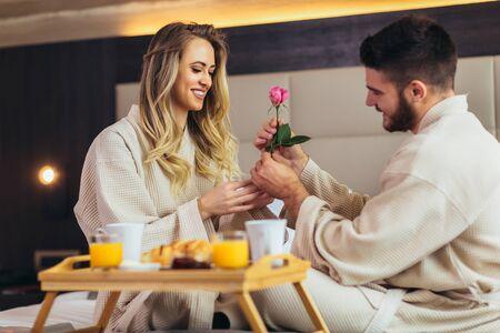 Young happy couple having breakfast in luxury hotel room Stock Photo - 137317104