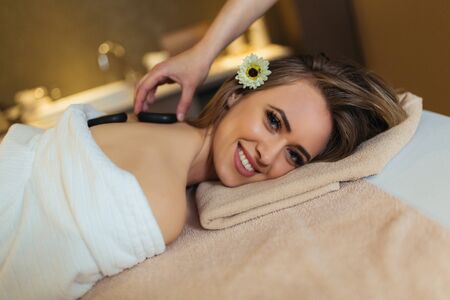 Cheerful young woman is enjoying back stone massage at spa.