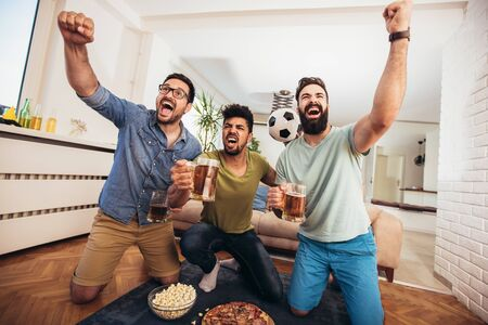 Happy male friends supporting football team at home
