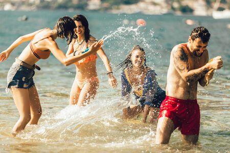 Szczęśliwi przyjaciele bawią się na plaży