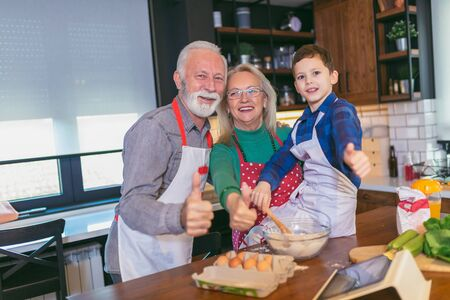 Young boy having fun with her grandparents in the kitchen