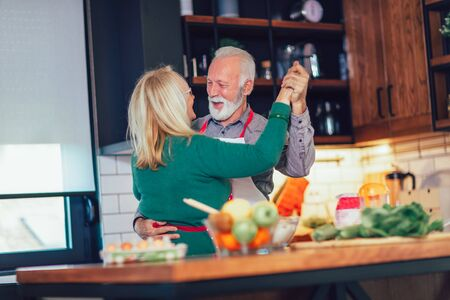 Beautiful senior couple is dancing and smiling while cooking together in kitchen Foto de archivo - 138047548