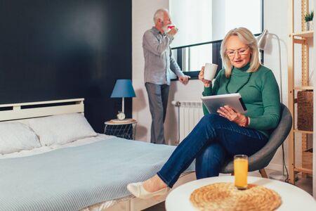 Senior couple in bedroom. Woman using a tablet, man drinking wine.  Zdjęcie Seryjne