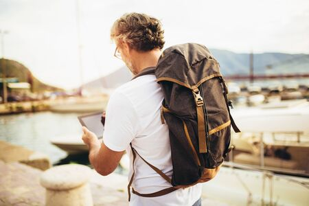 Smiling tourist mature man standing with digital tablet and backpack near the sea.