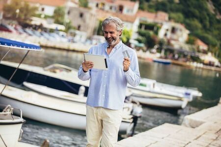 Mature man using digital tablet and credit card on the marina near the sea. Reklamní fotografie