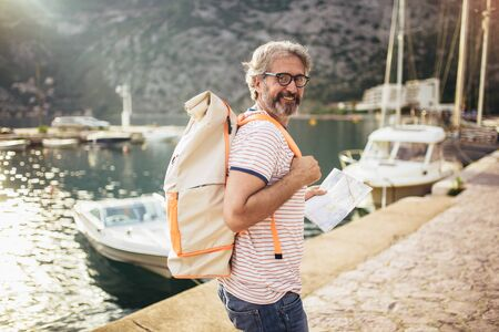Smiling tourist mature man standing with map and backpack near the sea. Reklamní fotografie