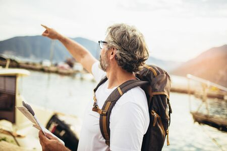 Smiling tourist mature man standing with map and backpack near the sea.