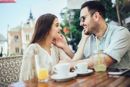 Beautiful loving couple sitting in a cafe enjoying in coffee and conversatio