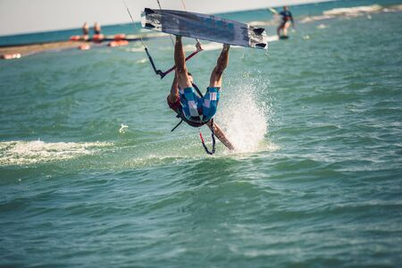 Professional kiter makes the difficult trick on a river. Kitesurfing Kiteboarding action photos man among waves quickly goes Imagens