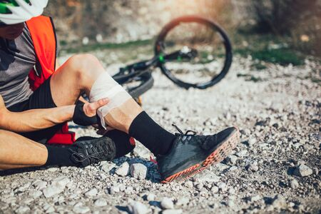 The biker fell from a bike, using a bandage from his first aid kit to help himself. Bicycle accident.  Zdjęcie Seryjne